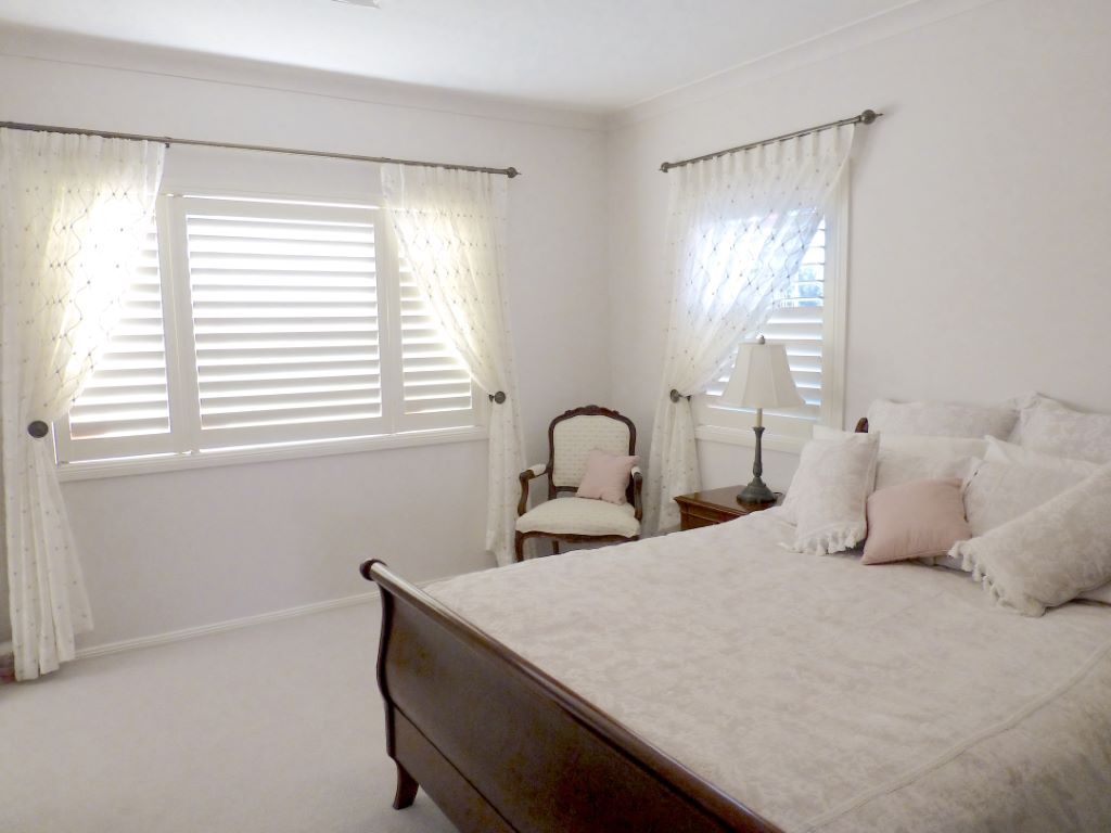 Feminine Bedroom with Shutters and Sheer Curtains